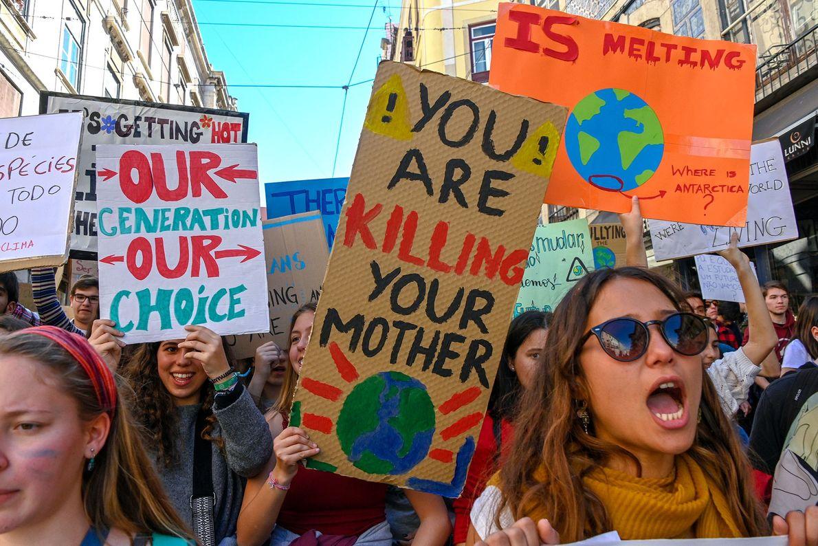 Portugiesische Studenten halten ihre Plakate vor dem Parlamentsgebäude hoch.