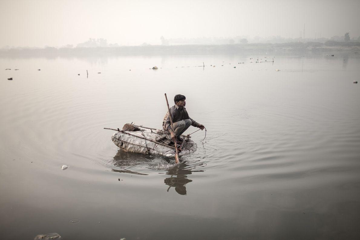 Ein obdachloser Junge fischt nach Münzen