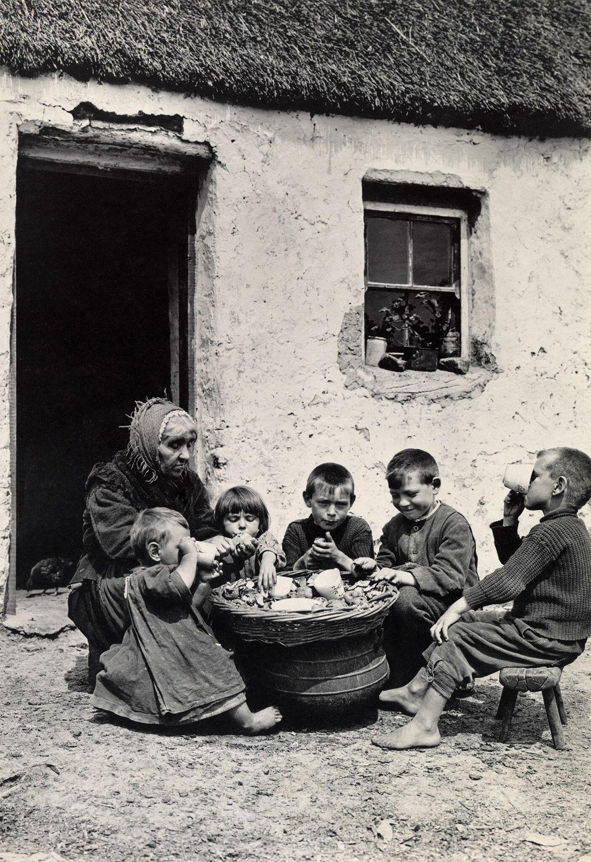 Irische Kinder sitzen draußen und essen Kartoffeln und Milch.