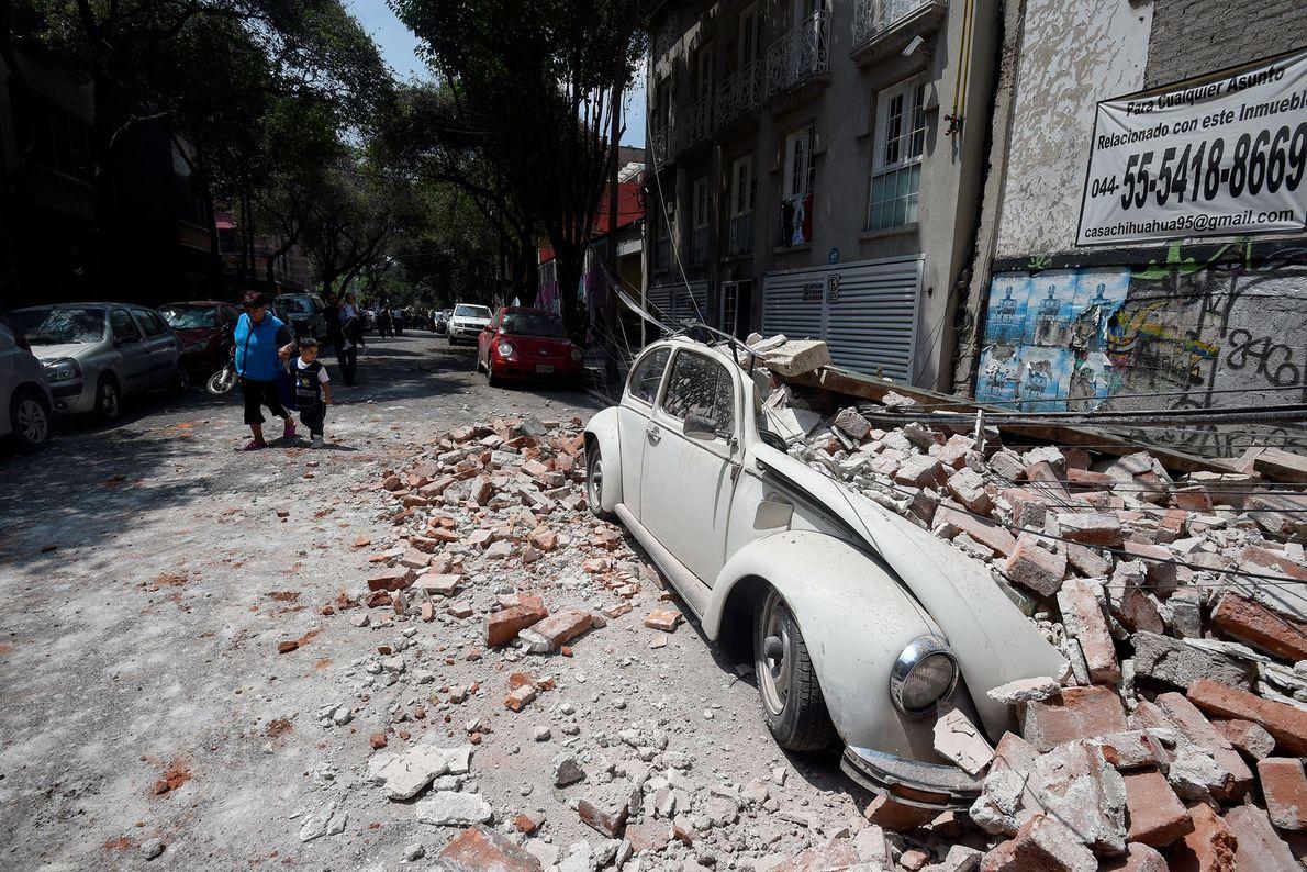 Ein Auto wurde von herabfallenden Ziegelsteinen eingedrückt, die sich während des Erdbebens von einem Gebäude lösten.