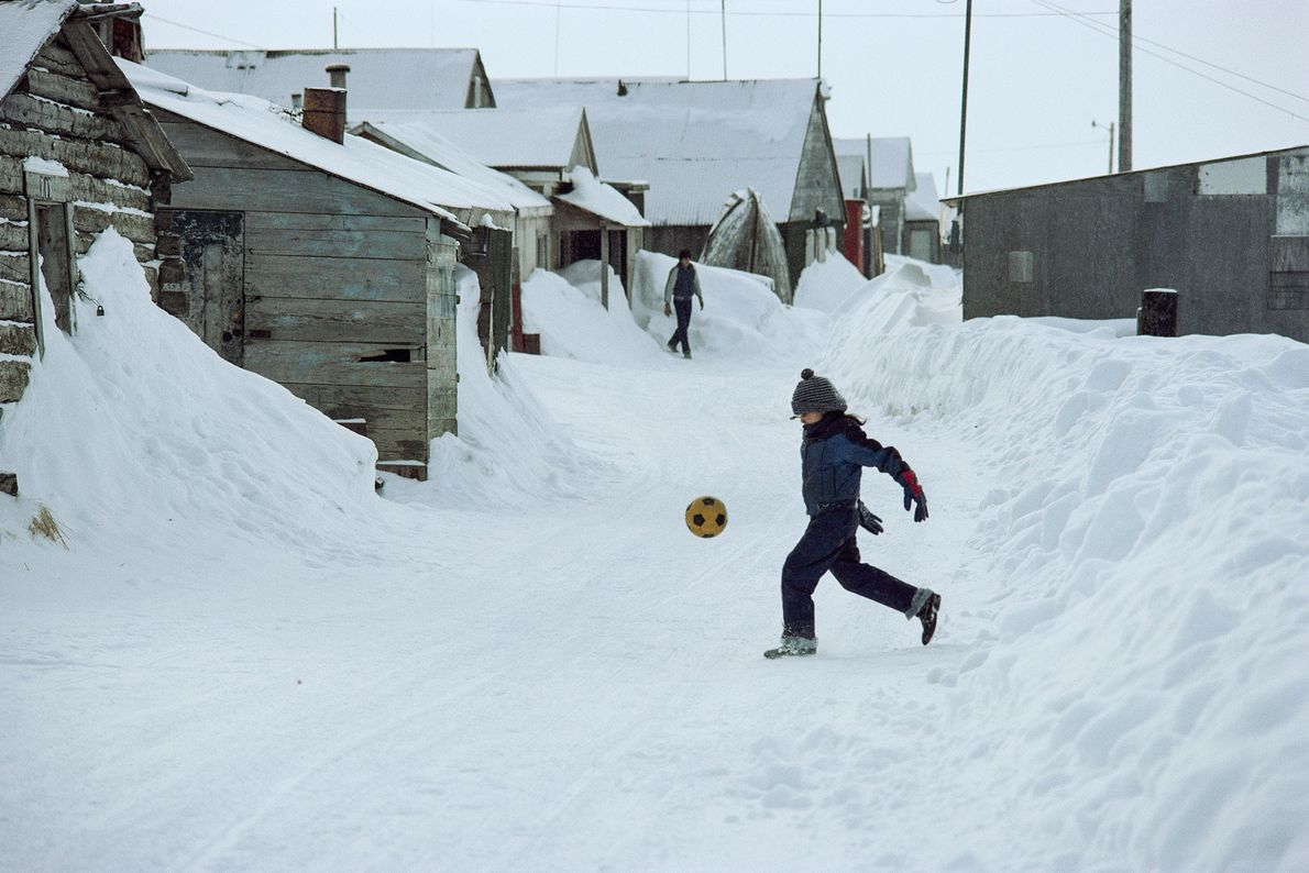 In Barrow im US-Bundesstaat Alaska tritt ein Junge einen Fußball durch die verschneiten Straßen.