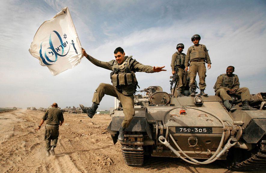 Ein israelischer Soldat springt von einem gepanzerten Fahrzeug. In der Hand hält er die Flagge zum ...