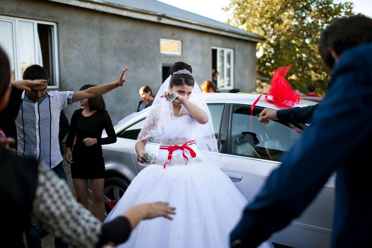 Foto von einer Braut, die weint, während ihre Familie um sie herumtanzt