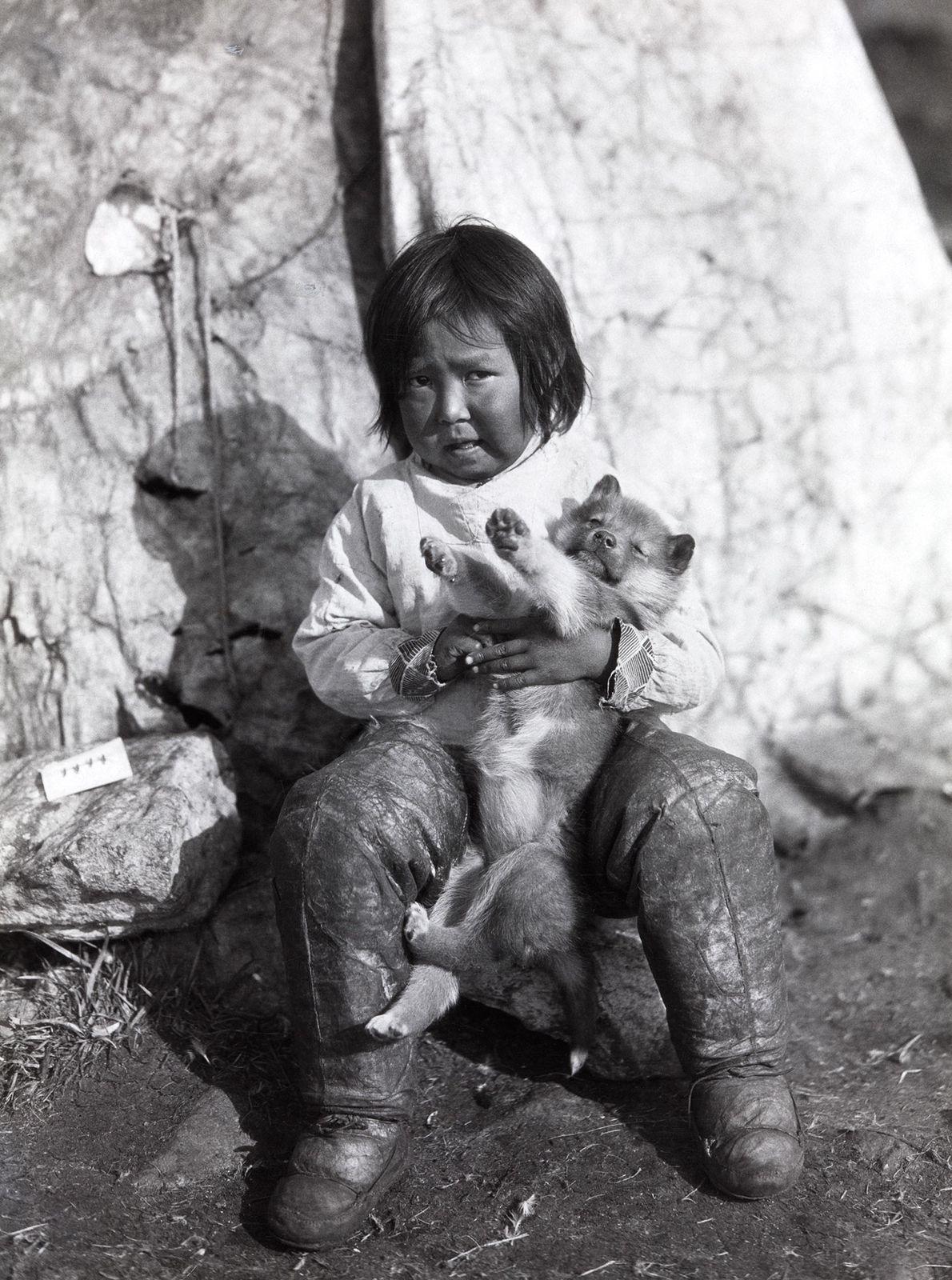 Inuit-Mädchen mit Welpen