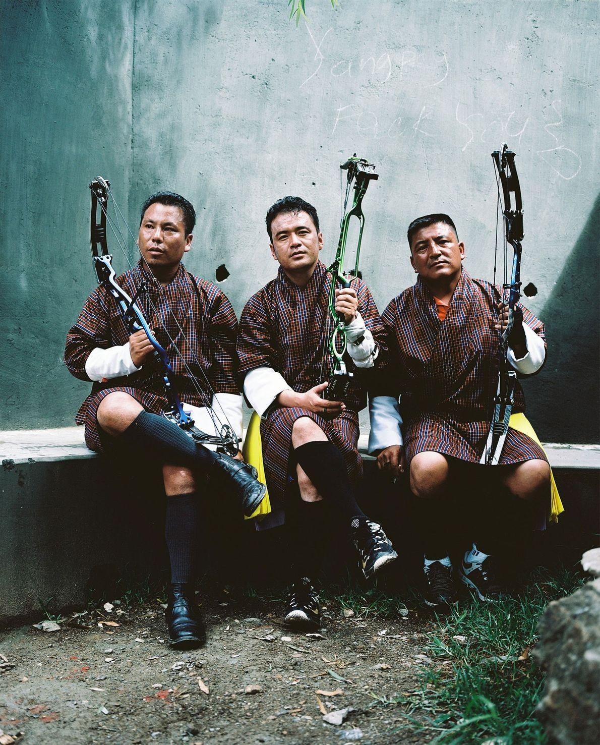 Während eines Bogenschießwettbewerbs in Paro machen diese drei Männer eine Pause. Von links nach rechts: Pema ...