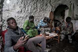 Senegalesische Einwanderer sitzen in einer Höhle in den oberen Bereichen der Hügel. Die Höhlen von Sacromonte ...