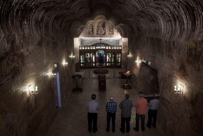 Kirchgänger besuchen einen Sonntagsgottesdienst in einer unterirdischen orthodoxen Kirche, die 1993 von der serbischen Gemeinschaft gebaut ...