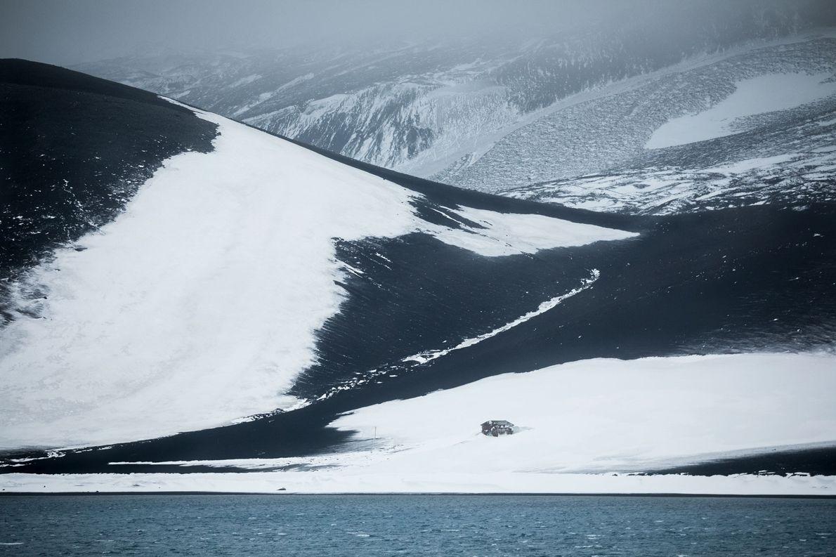 Eine verfallene Hütte steht tief in der Caldera einsam an einem großen Hang. Sie befindet sich …