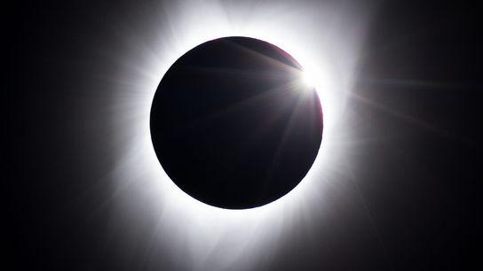Die ersten Strahlen der Sonne erscheinen hinter dem Mond, während die Korona immer noch sichtbar ist. ...