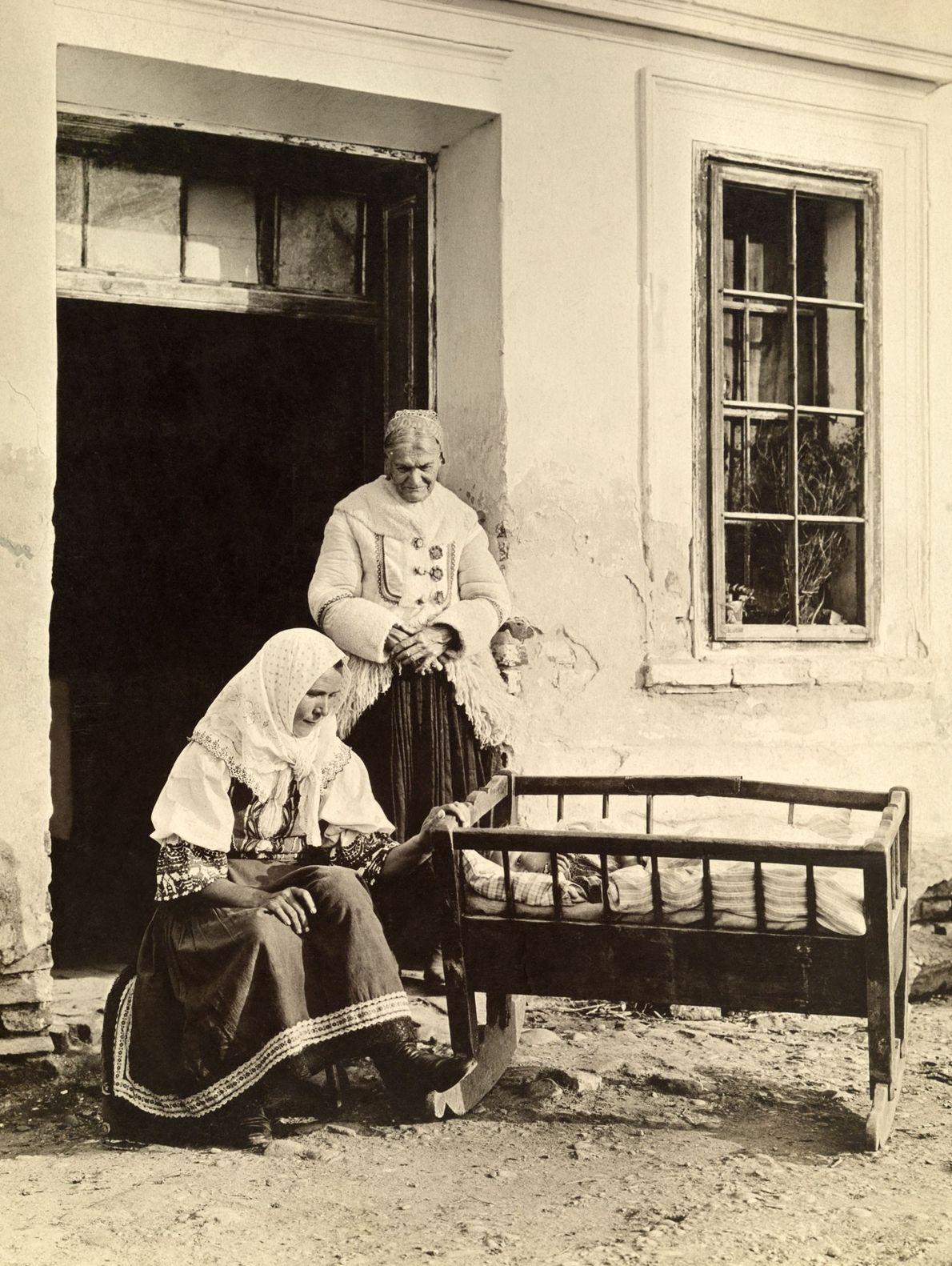 Eine slowakische Mutter wiegt ihr Kind in einer Krippe vor dem Haus in Böhmen, während die ...
