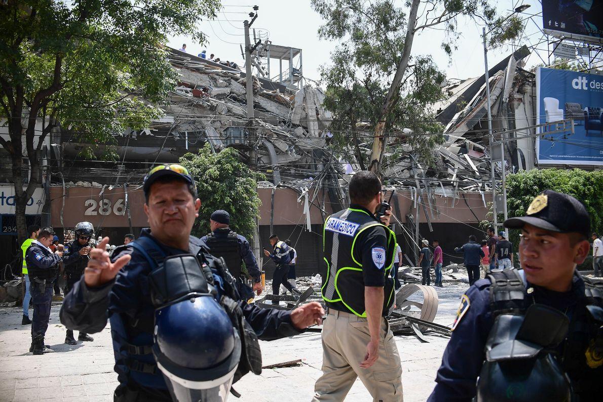 Polizisten sperren einen Bereich ab, der durch das Erdbeben in Mitleidenschaft gezogen wurde.