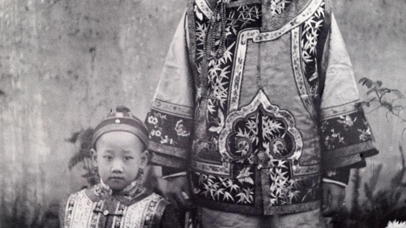 Eine chinesische Mutter und ihr Kind tragen die traditionelle Kleidung der Mandschurei, einer Region ganz im ...