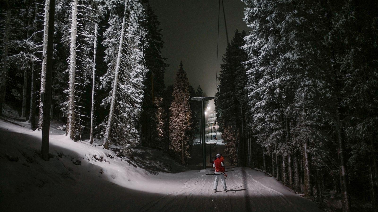 Ein Skifahrer nimmt den Schlepplift zwischen riesigen Bäumen hindurch zum oberen Ende der Nachtpisten von Rogla.