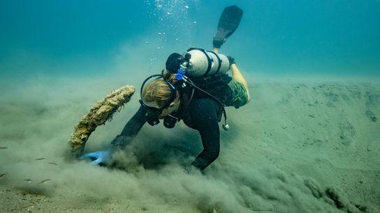 Frederick Hanselmann, Co-Leiter des Projekts, wischt Sand von dem Anker. Er stammt aus dem 16. Jahrhundert ...
