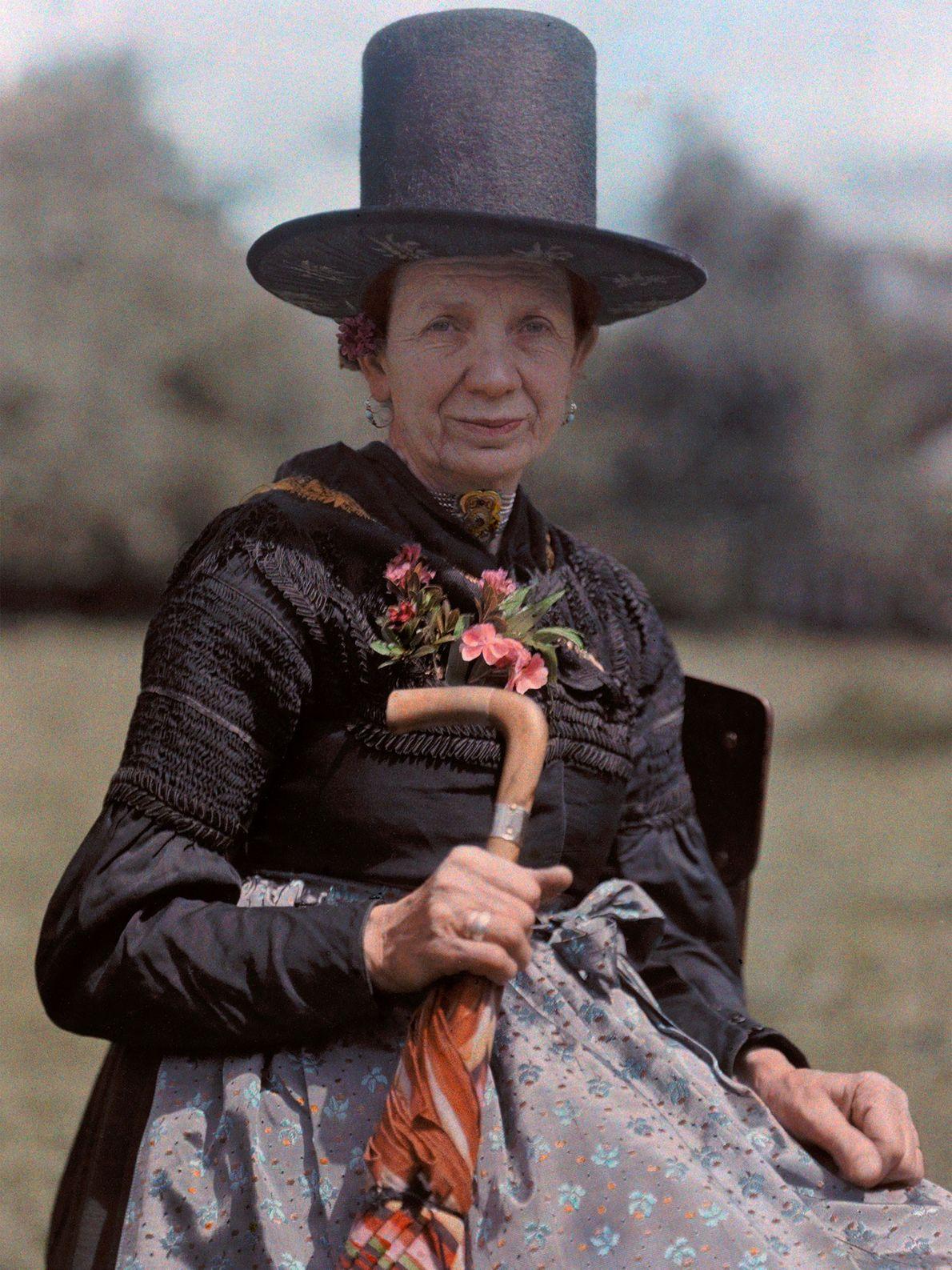 Eine Frau aus dem österreichischen Bischofshofen posiert mit einem Hut, unter dessen Krempe Zierelemente zu sehen ...