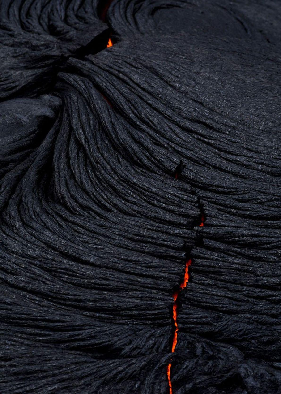 Aus den schmalen Rissen erkaltender Lavaströme leuchtet noch flüssige Lava hervor.