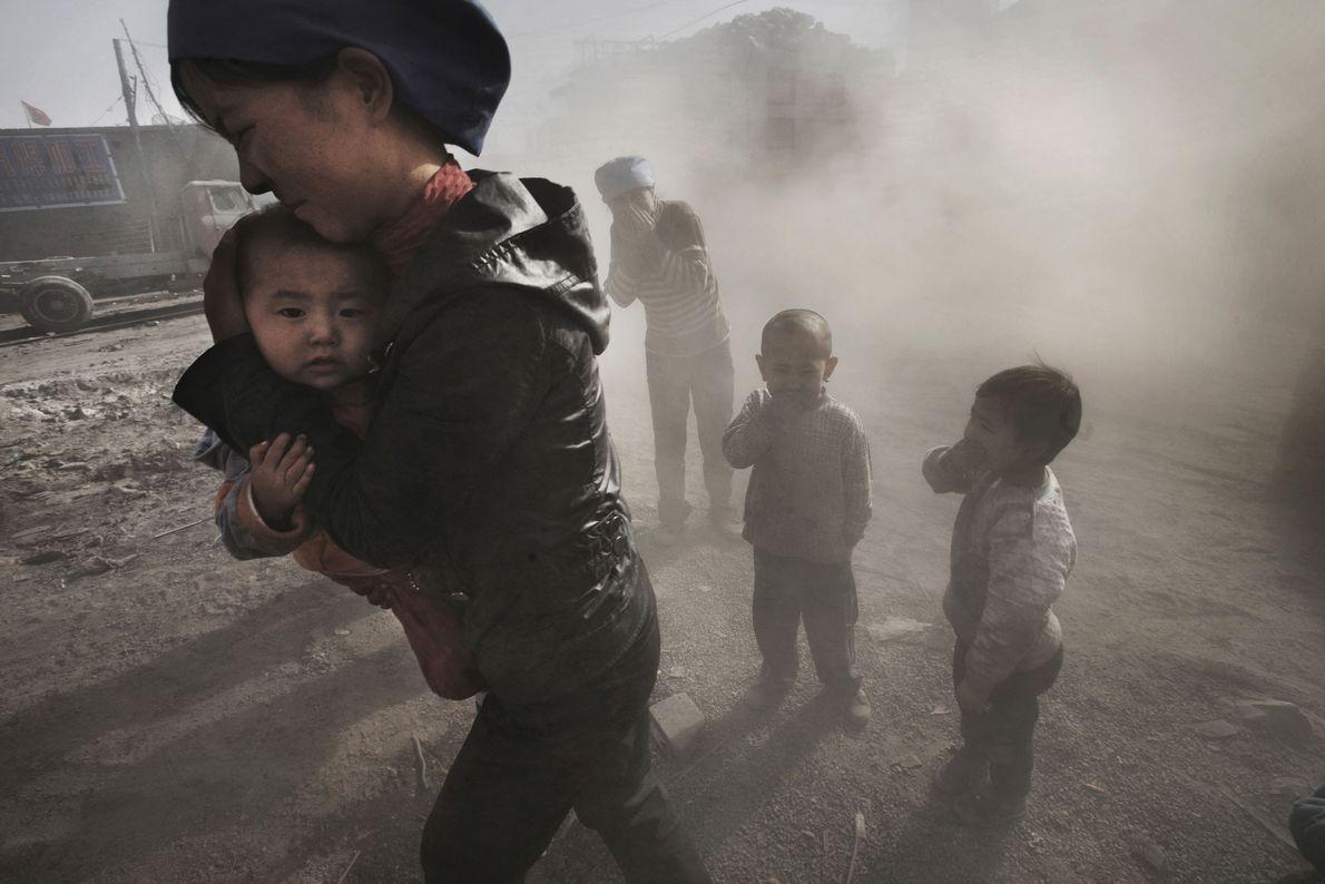 Der mit Kohle beladene Lkw zieht eine Staubfahne hinter sich her, die die Bewohner von Wuhai ...