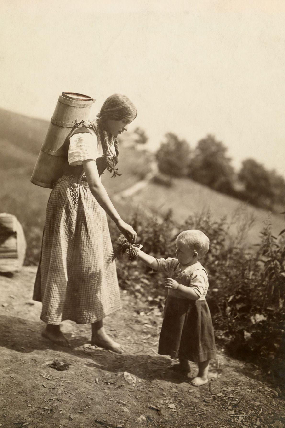 Eine Schweizer Mutter greift nach den Blumen, die ihre junge Tochter gesammelt hat.
