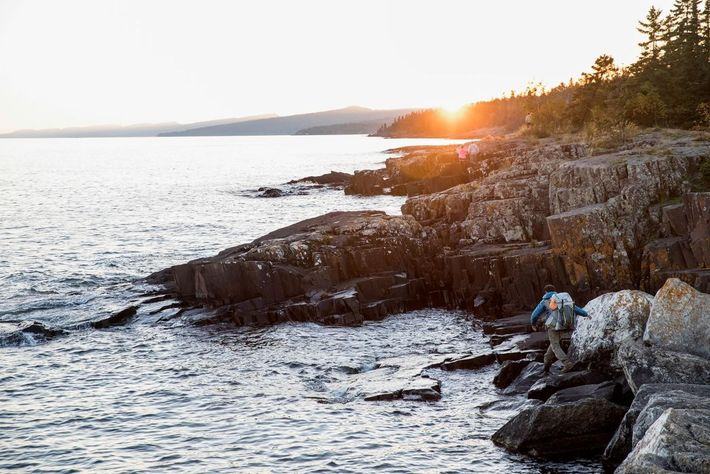 Dupre wandert an der felsigen Uferlinie des Lake Superior entlang.