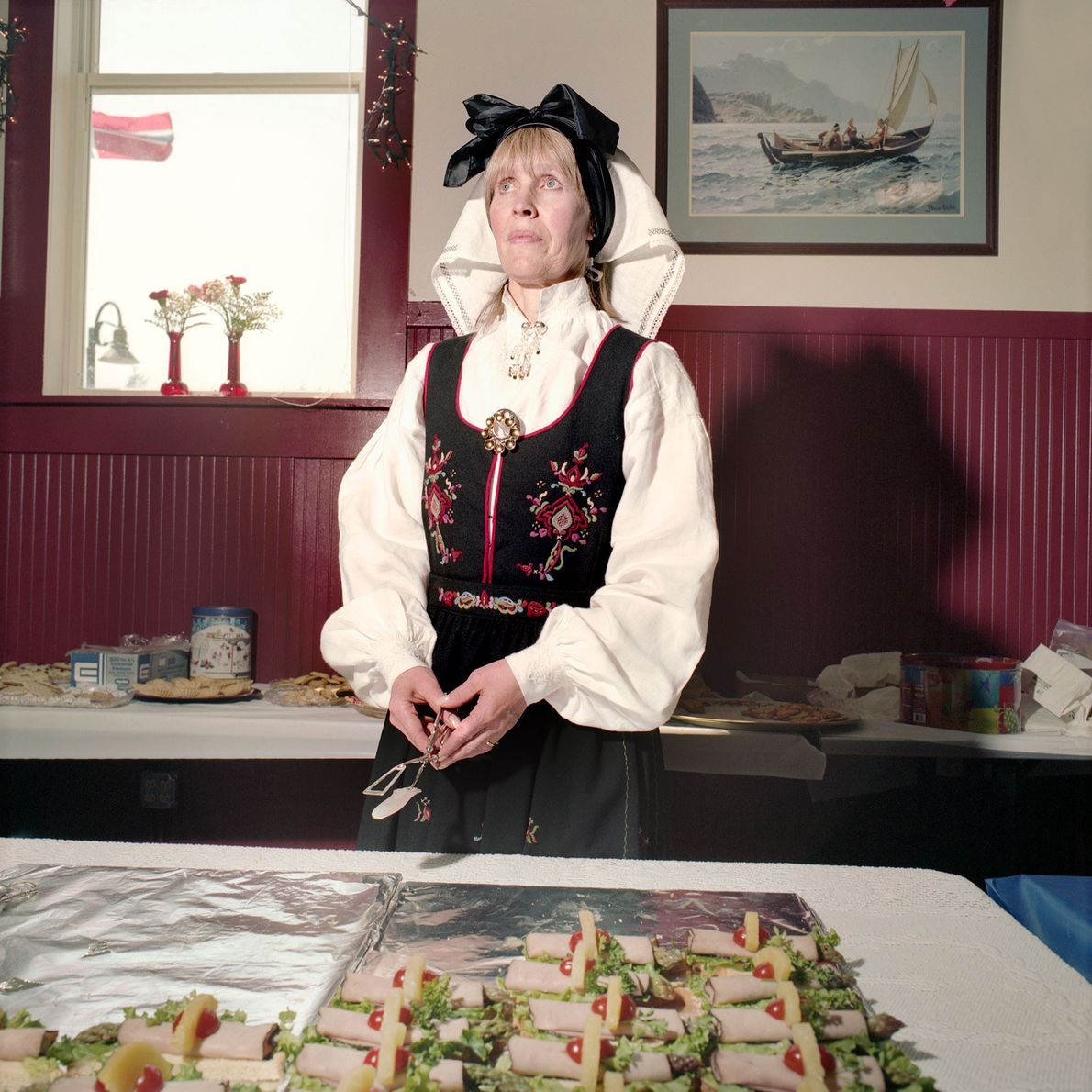 Frau in Tracht vor Buffet
