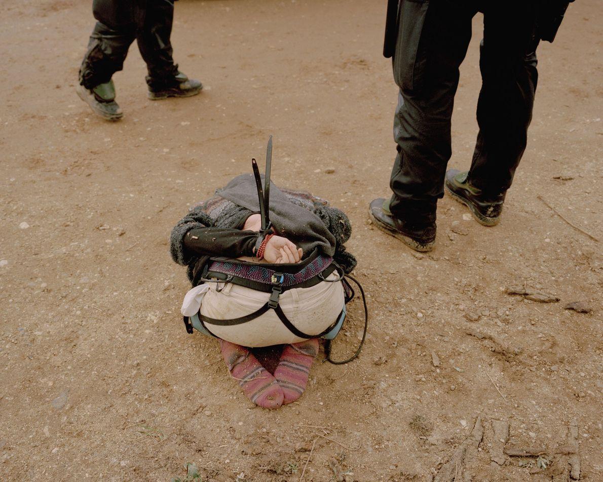 Eine von der Polizei gefesselte Aktivistin kniet am Rande des Waldes.