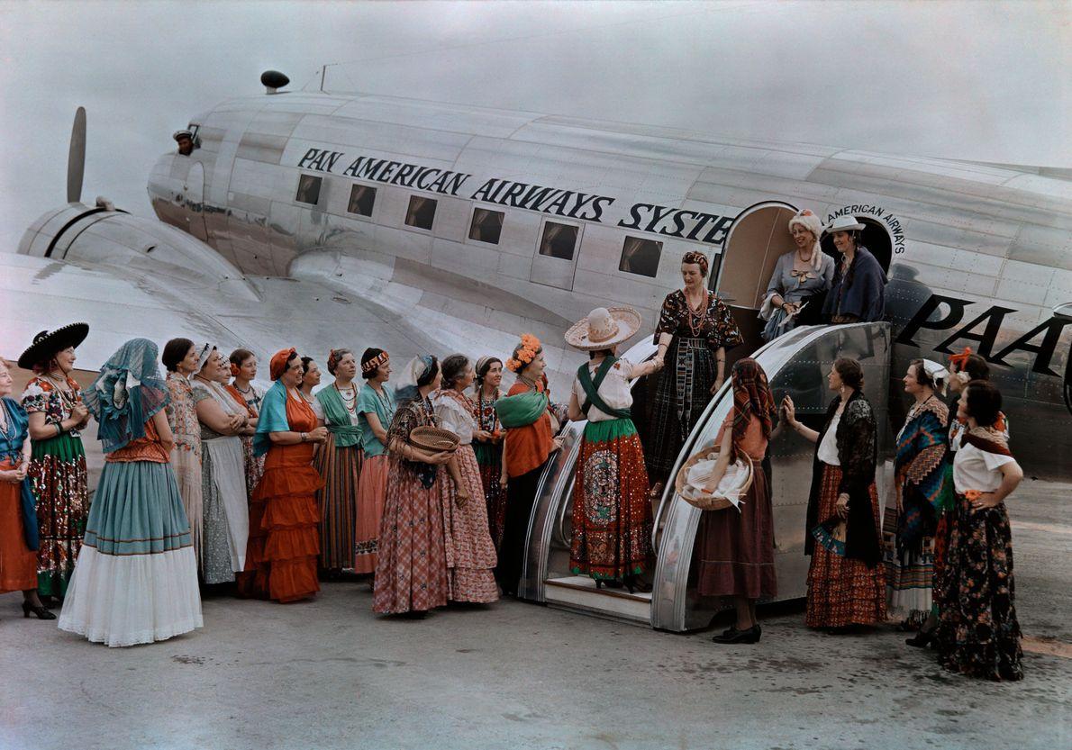 BROWNSVILLE, TEXAS, USA: 1938 Frauen in traditioneller Tracht begrüßen weibliche Passagiere aus einer Maschine von Pan Am.