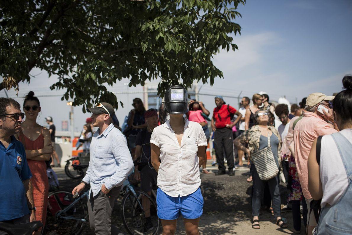 Eine Frau hat in Red Hook, Brooklyn, eine Schweißmaske aufgesetzt, um ihre Augen bei der Beobachtung ...