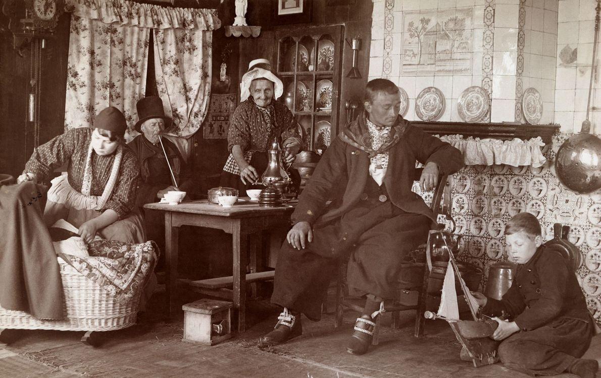 Drei Generationen einer Familie sitzen in den Niederlanden rund um den Esstisch in ihrem Zuhause. 1915.
