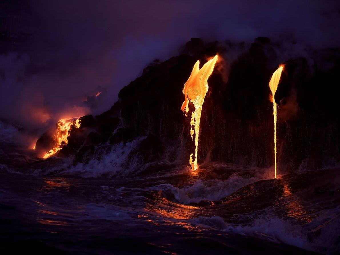 Ein Lavafluss ergießt sich während der Dämmerung ins Meer.