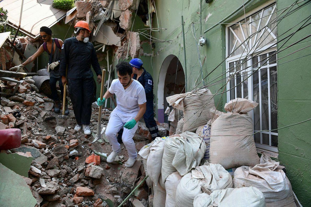 Menschen suchen zwischen Schutt und Trümmern nach Opfern.