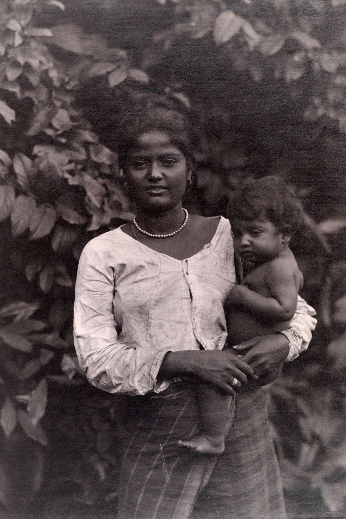 Eine ceylonesische Mutter stützt ihr Kind auf der Hüfte ab.