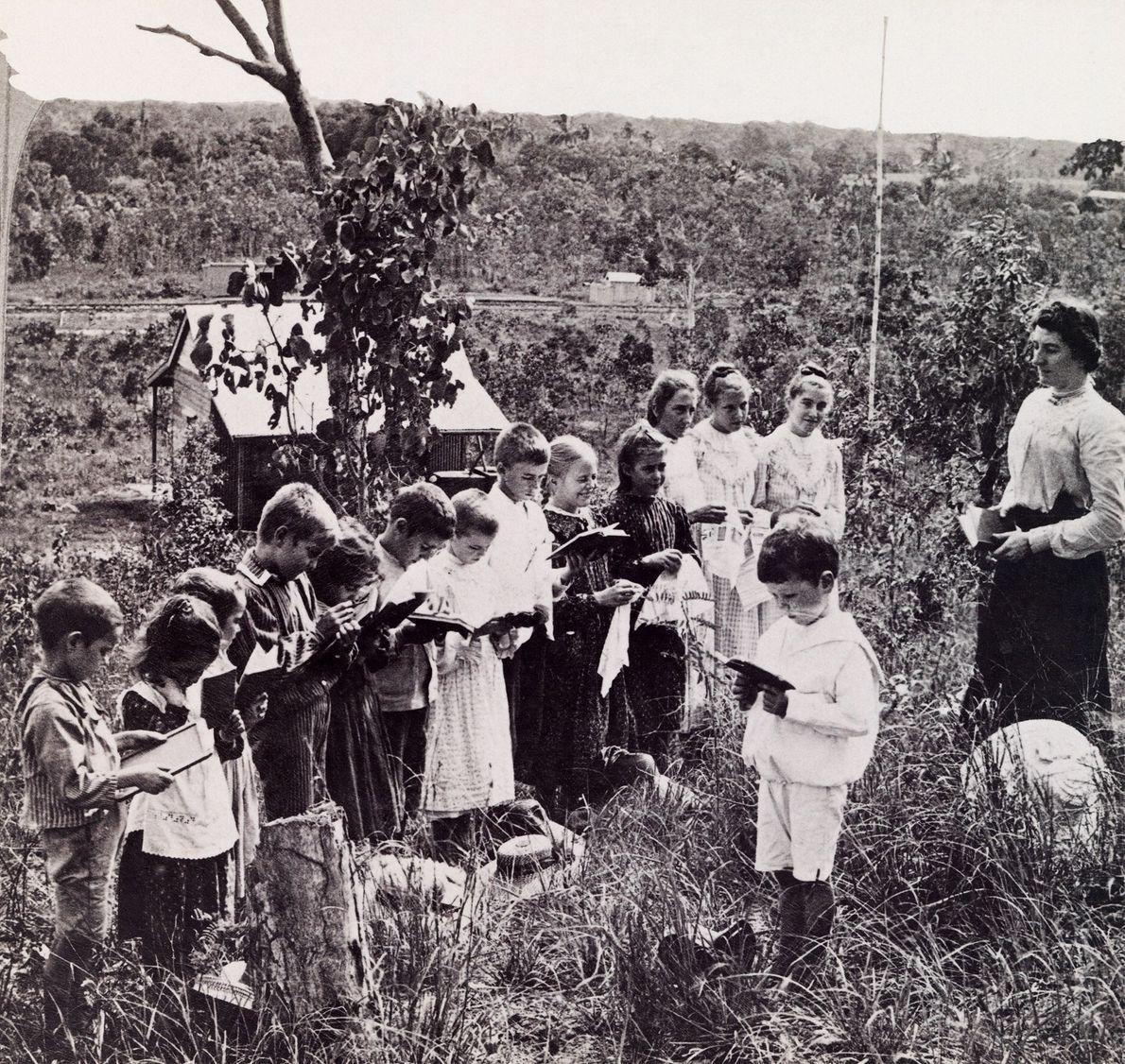 Eine Lehrerin und ihre Schüler stehen zum Lesen draußen in der Natur.