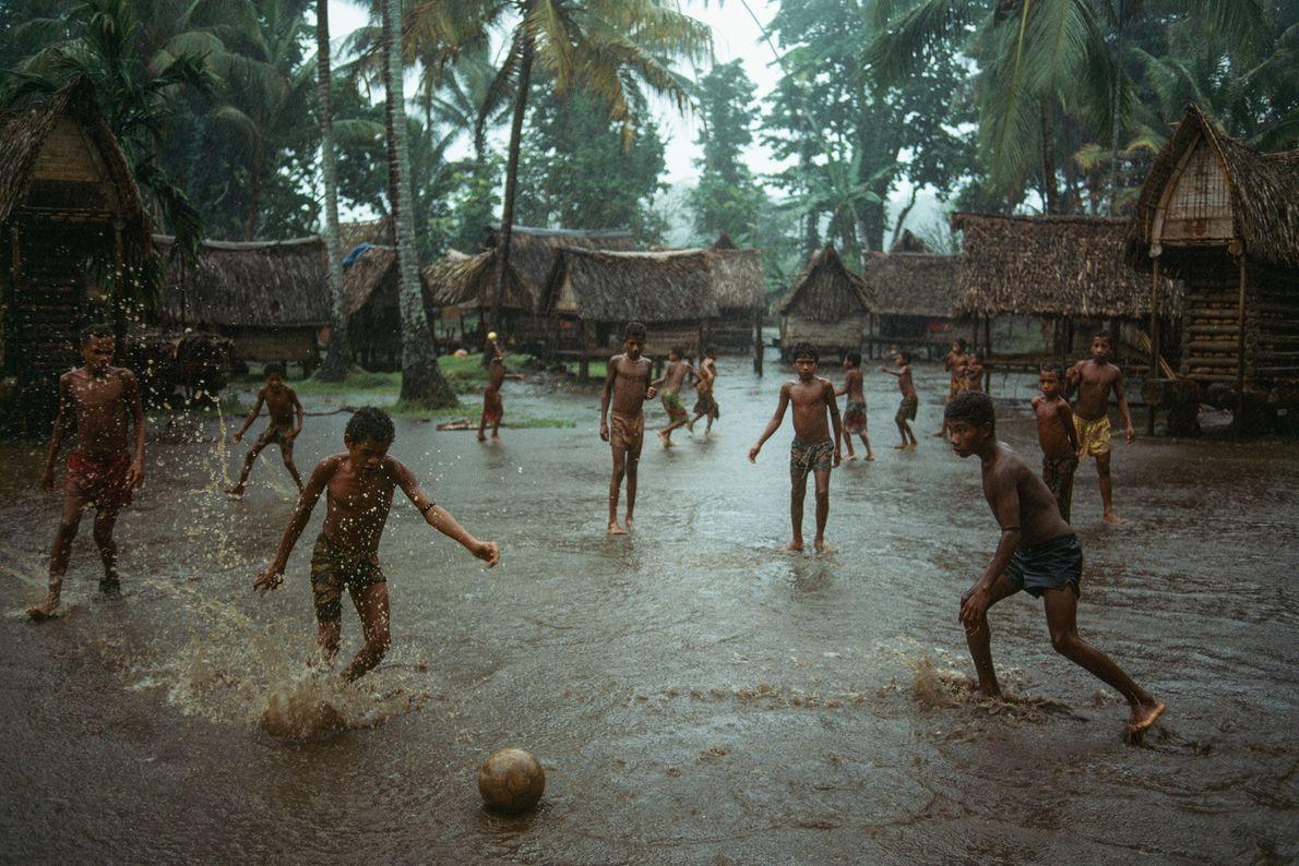 Auf Kiriwina, der größten der Trobriand-Inseln in Papua-Neuguinea, spielen Jungs in einem leicht überschwemmten Dorf Fußball.
