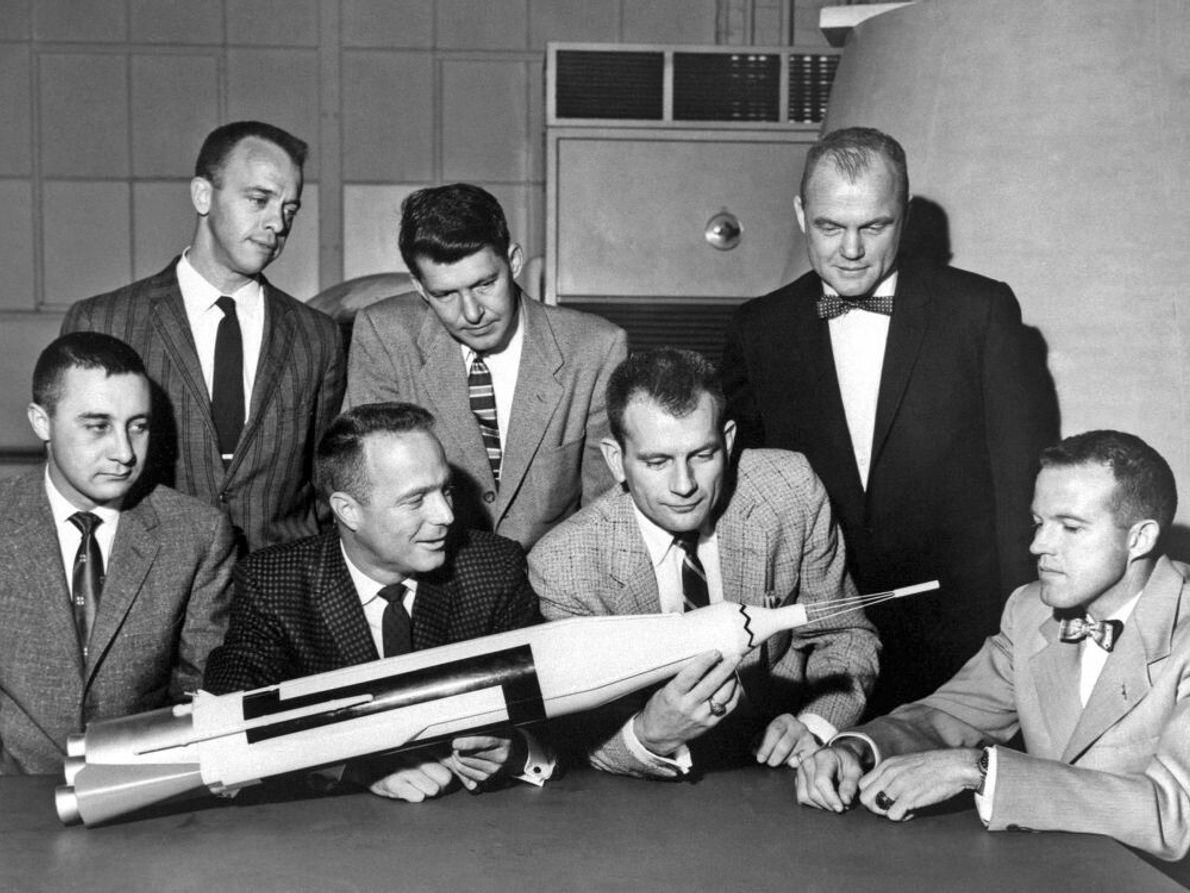 Die Astronauten posieren mit einem Modell der zusammengesetzten Raketenstufen. An der Spitze befindet sich die Kapsel. ...