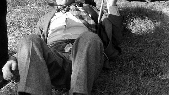 Ein junger, angetrunkener Vater mit einem zerrissenen Schirm und Sonnenbrille liegt während des Vatertages auf einer ...