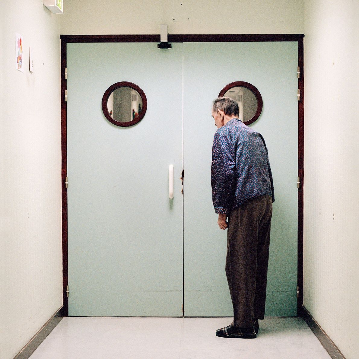 A resident stands in front of the ward's locked exit.