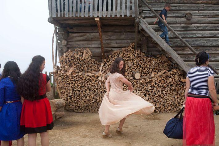 Foto eines Mädchens, welches sich in ihrem pinken Kleid vor dem Feuerholz dreht.