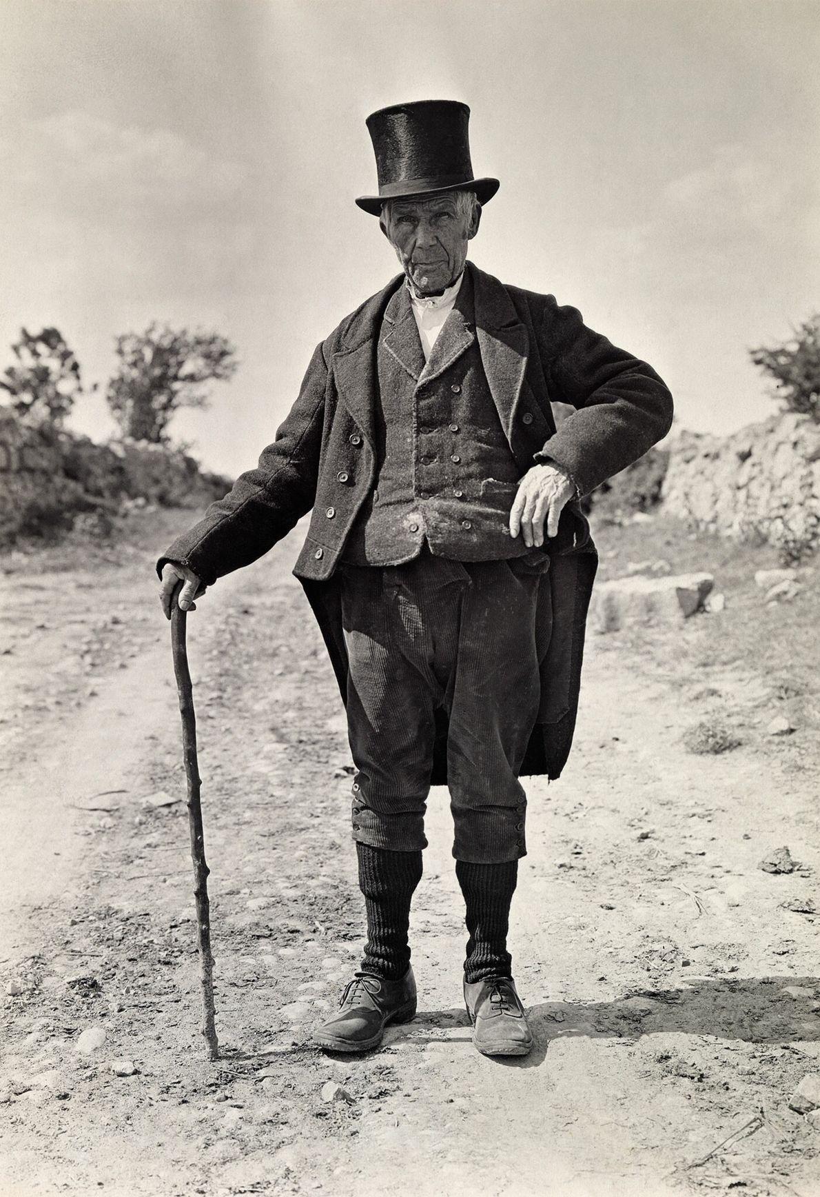 Ein Mann in Wollweste, Frack und Zylinder posiert für ein Porträt in Irland.
