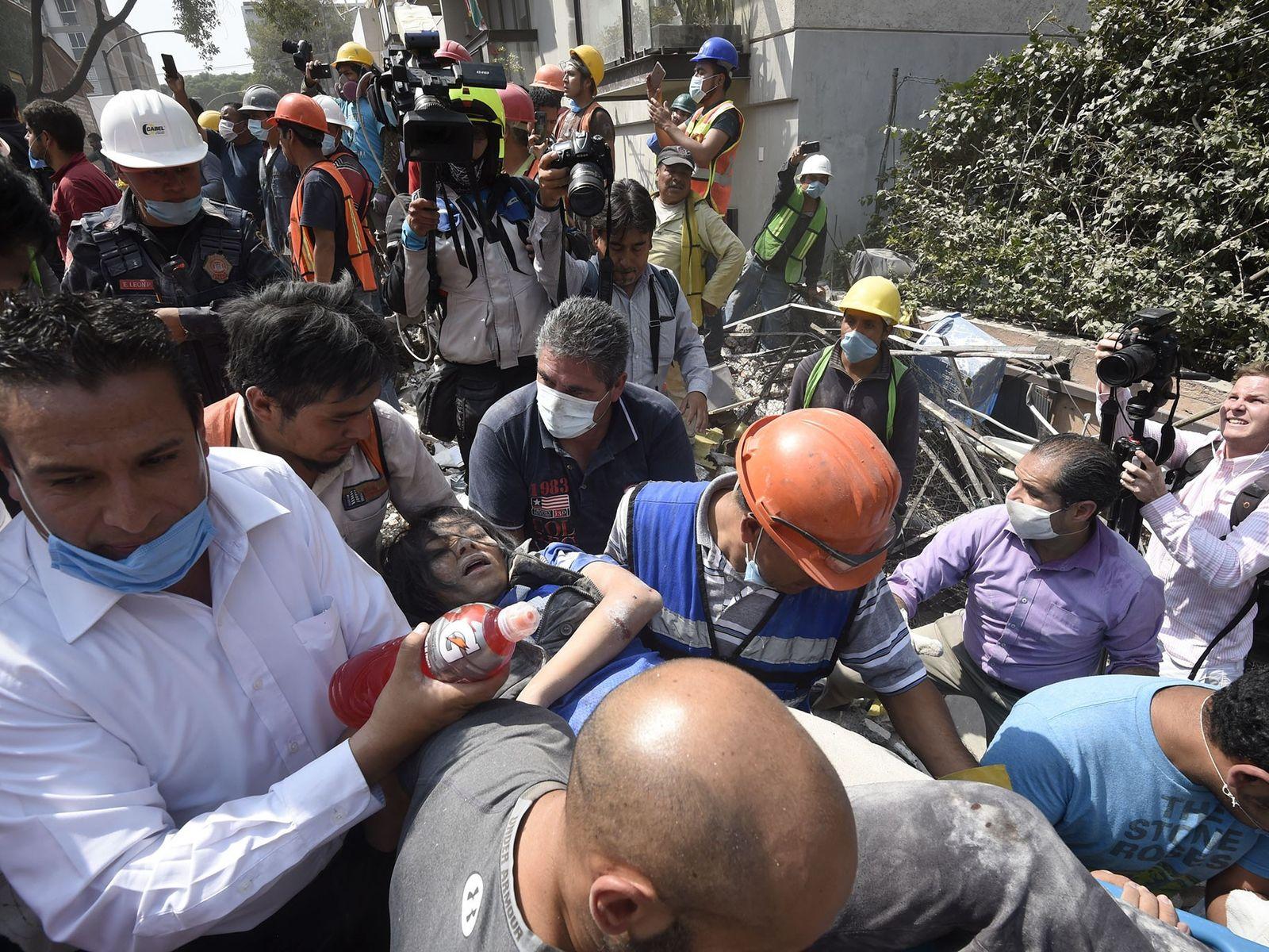Eine Frau, die nach dem Erdbeben aus den Trümmern gezogen wurde, wird weggetragen.