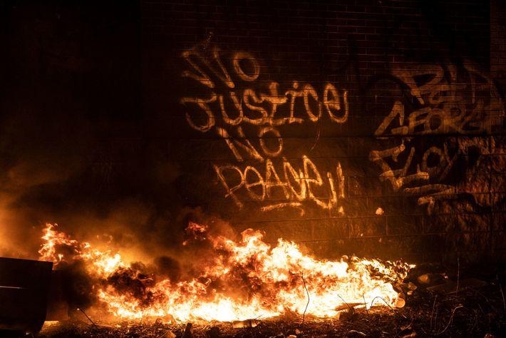 An der Seite des brennenden Polizeireviews drücken Graffiti ihre Unterstützung für die Proteste aus.