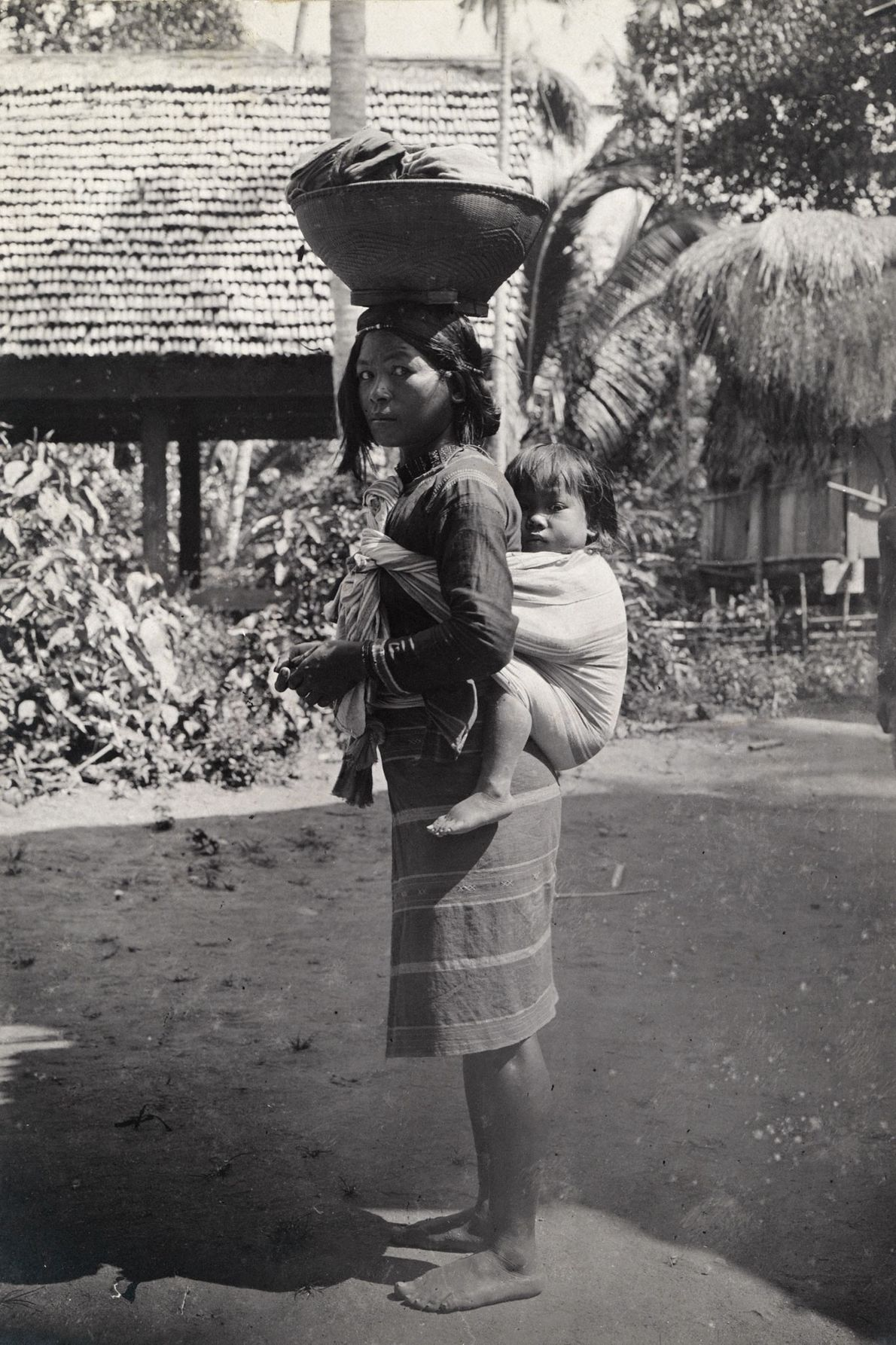 Auf der Philippineninsel Luzon trägt eine Frau ein Kind auf dem Rücken, während sie auf ihrem ...