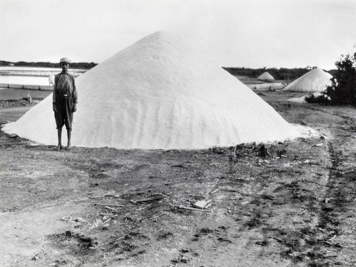 Ein Junge steht neben einem Salzhaufen. Das Mineral wird aus verdunstetem Meerwasser gewonnen.