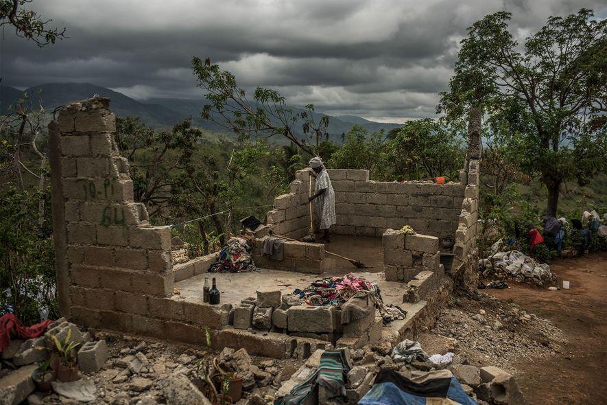 Frau säubert zerstörtes Haus