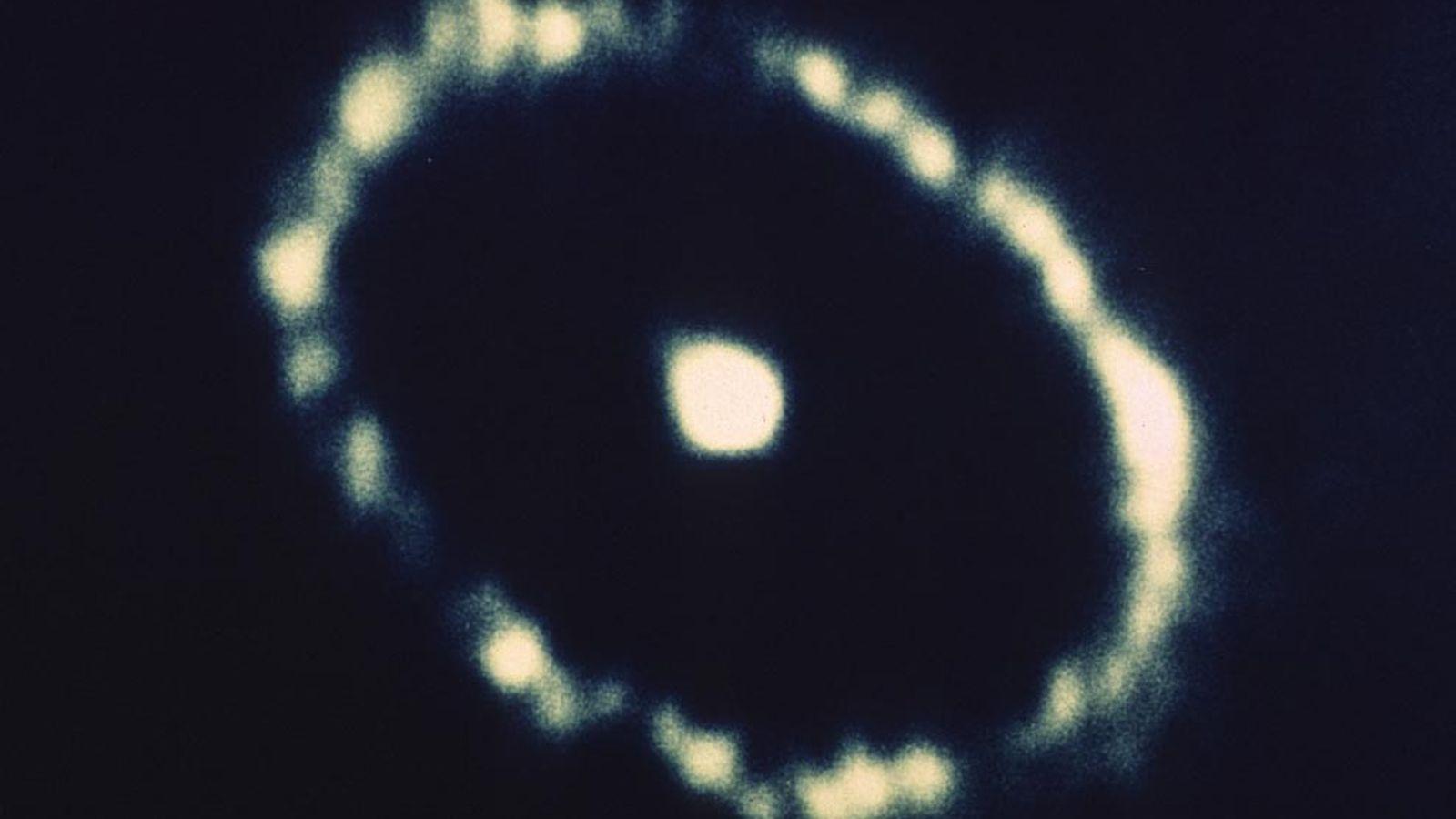 Ein Ring aus leuchtenden Partikeln umgibt die Überreste der Supernova 1987A in der Großen Magellanschen Wolke. ...