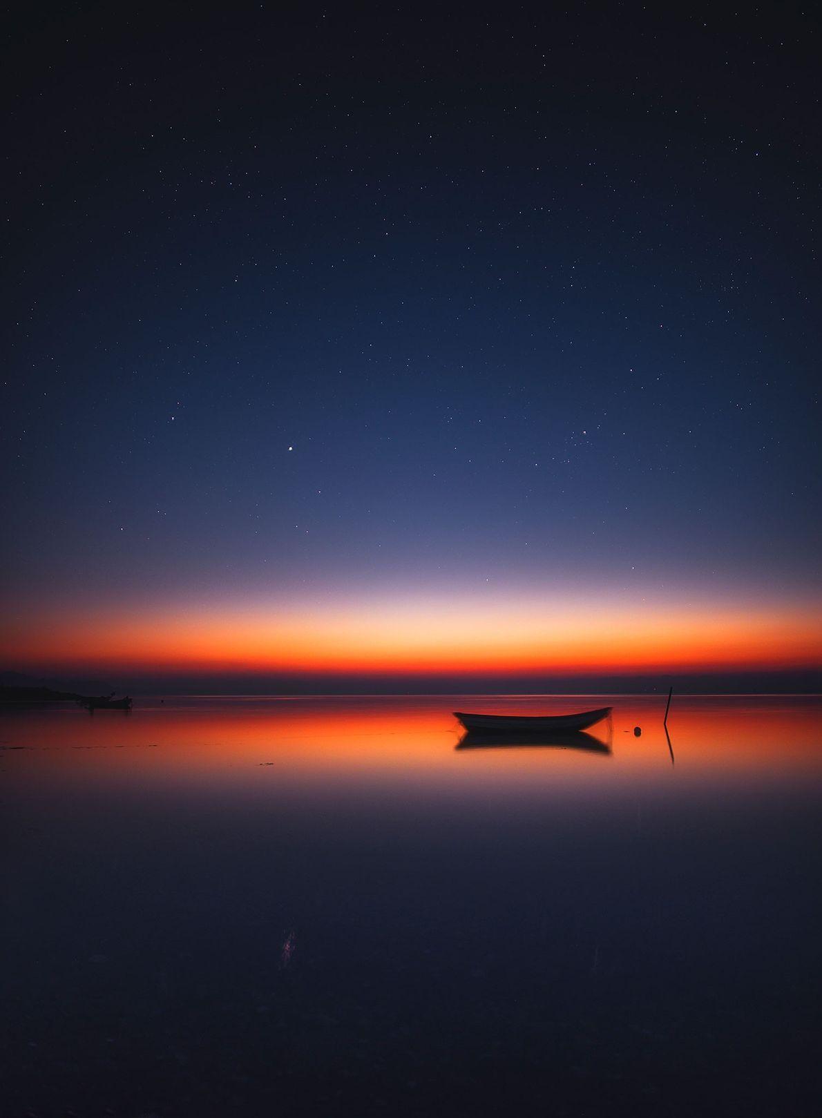 Der dunkle Sommerhimmel beginnt über dem Limfjord im dänischen Nykøbing Mors orange zu leuchten.