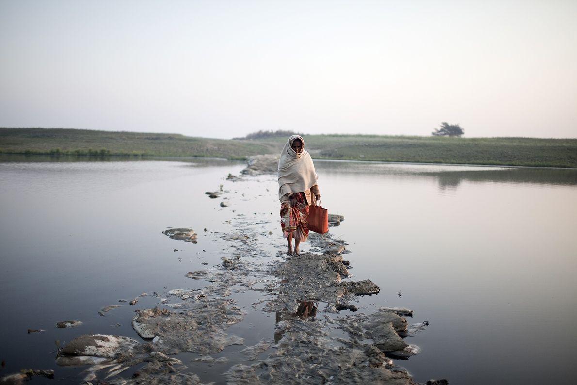 Eine Frau überquert einen kleinen Kanal des Ganges