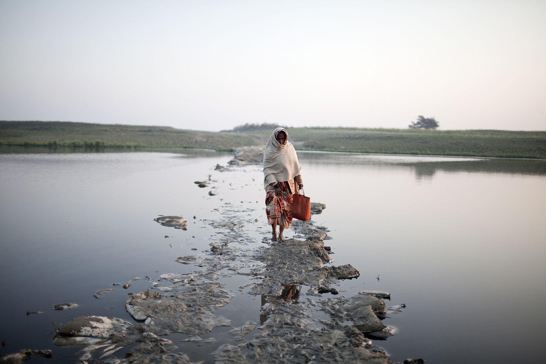 Eine Frau überquert einen kleinen Kanal des Ganges auf einer überschwemmten Brücke aus Müll.