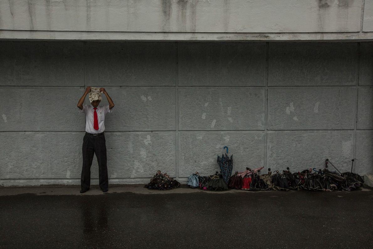 Mann schützt sich vor Regen