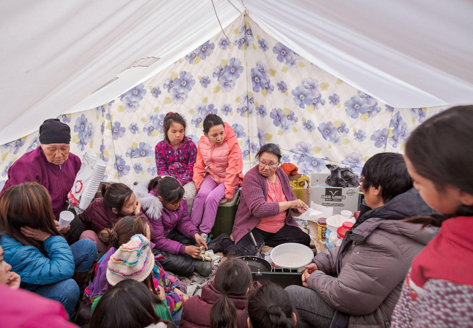 Tagoonak Qavavauq, eine der Ältesten, bringt Kindern auf einem Schulausflug bei, wie man Bannock-Brot zubereitet. Das ...