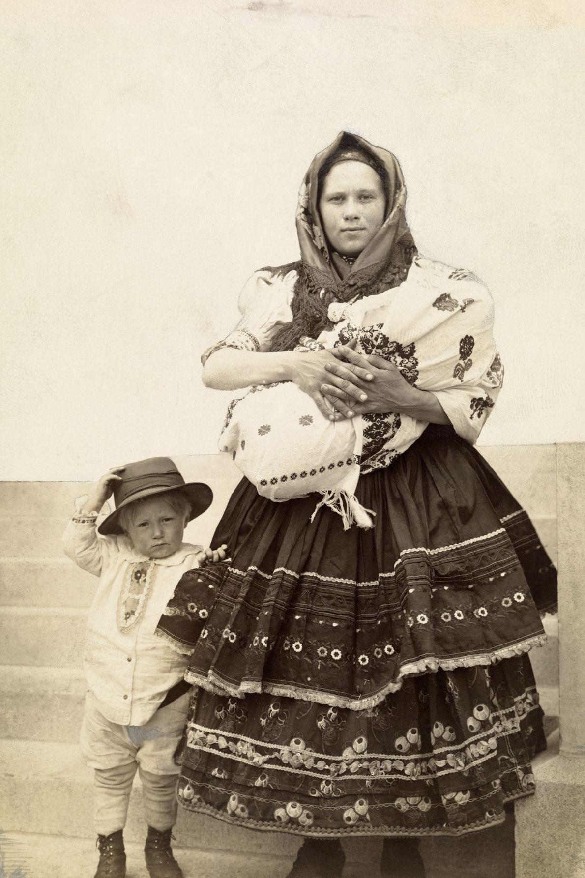 Eine ungarisch-slowakische Einwanderin in den USA hält ihr jüngstes Kind im Arm, während ihr Sohn neben ...